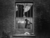 A suffragette looks through a window on Holloway prison